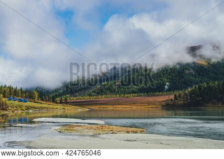 Scenic Autumn Landscape With Reflection Of Gold Sunlight In Mountain Lake And Mountains In Low Cloud