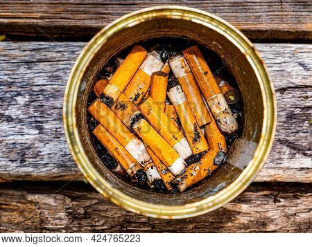 Ashtray From A Tin Can With Cigarette Butts On A Wooden Table.