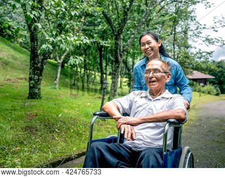 Grandfather In A Wheelchair With Granddaughter Enjoying Nature In The Park. Family Life On Vacation.