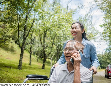 Cheerful Disabled Senior Man Talking On Smartphone While Granddaughter Pushing A Wheelchair In The P