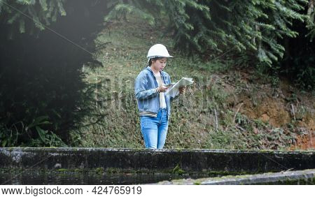Female Ecologist In Safety Hat Working And Controlling A Quality Of Water At Wastewater Treatment Pl