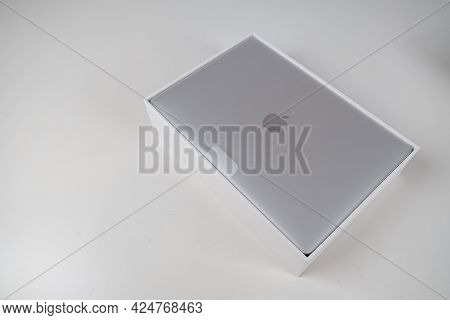 Unboxing A Silver Macbook Air On A White Table. Apple Laptop