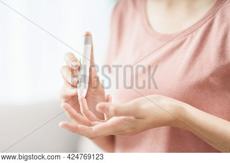 Asian Woman Using Lancet On Finger For Checking Blood Sugar Level By Glucose Meter, Healthcare And M