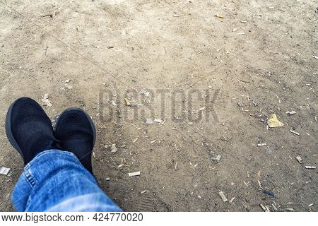 Feet In Sneakers And Cigarette Butts Thrown To The Ground