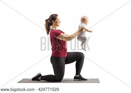 Young mother kneeling on an exercise mat and holding her baby isolated on white background