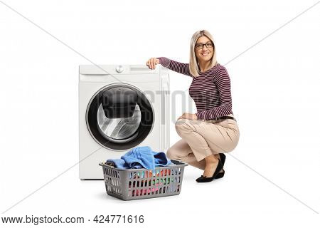 Young woman kneeling next to a washing machine and looking at camera isolated on white background
