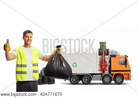 Waste collector with a garbage truck holding a plastic bin bag and showing thumbs up isolated on white background