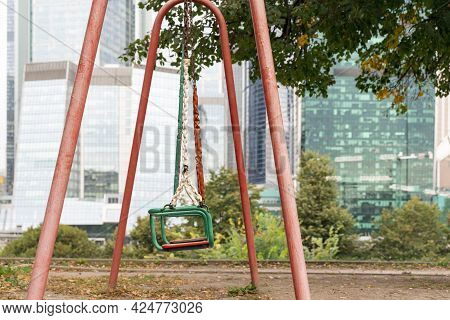 Weird Worn-out Children's Swing Against The Backdrop Of Modern Skyscrapers.