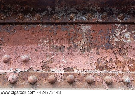 Flaking Paint On A Rusty Riveted Bridge. Old Rivets On The Bridge.