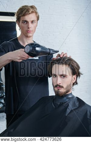Hairstylist does the hairstyle and styling with dryer, dries hair to a handsome male client. Barbershop.