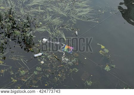 09.05.2020 Moscow, Russia. Dirty Dark River Surface Contaminated With Plastic