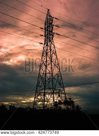 Power Lines And Tall Electrical Pylon Against The Evening Clouds In The Background.