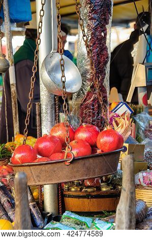 Display Of Pomegranates Inside An Old Metal Weighing Scale Hung With Rusty Chains And A Ladle Spoon