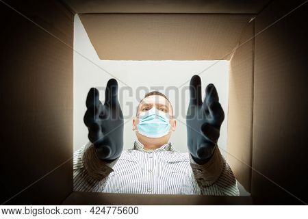 A Man In A Medical Mask And Gloves Takes Something Out Of A Box. Bottom View. Get Something Out Of A