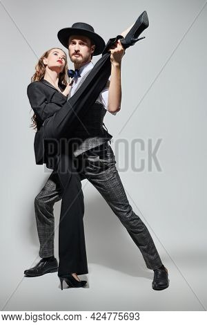Beautiful couple of young people in love dancing passionate tango. Sexual girl and handsome man in love. Fashion and love. Full length portrait on a grey background.