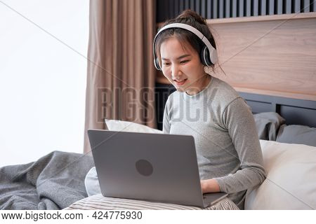 Young Asian Woman With Headphone Put Laptop On Pillow To Typing Business Project And Checking Social