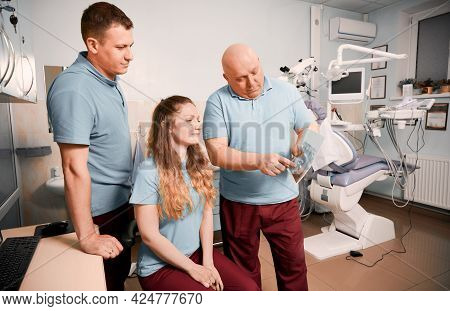 Male Stomatologist Pointing At Dental Scan While Working With Colleagues In Dental Office With Moder