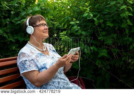 Grandmother In Headphones With A Tablet Listens To Music. An Elderly Woman In Headphones With A Tabl