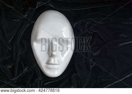 The Mask Of A Person's Face Is White On A Background Of Black Crumpled Velvet. A Theatrical Mask. A