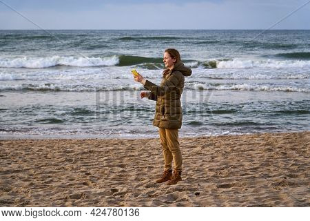 Winter Vacation At The Sea With A Phone. Hike In The Fall. On The Beach In A Jacket And A Backpack.h