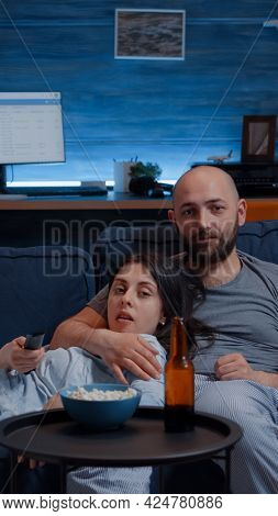 Relaxed Couple At Home Sitting On Couch Watching Tv Shows And Eating Popcorn Drinking Beer Switching