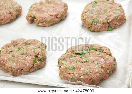 Raw beeburger beef patties on a oiled greaseproof paper on a baking sheet poster