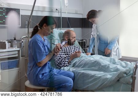 Sick Man Patient Resting In Bed Discussing With Medical Nurse Explaining Disease Symptom While Writi