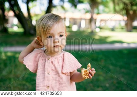 Little Girl With A Bitten Pancake In Her Hand