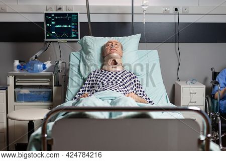 Hospitalized Senior Laying Unconscious In Hospital Room Bed Wearing Neck Brace Collar Having Serious