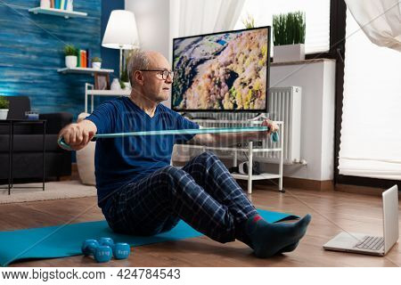 Retirement Senior Man Sitting On Yoga Mat With Leg In Crossed Position Stretching Arms Muscles Using