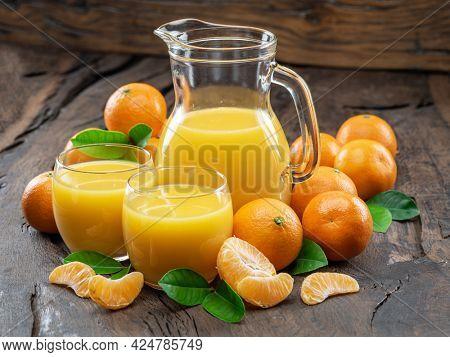 Orange tangerine fruits and fresh tangerine juice on dark wooden background.
