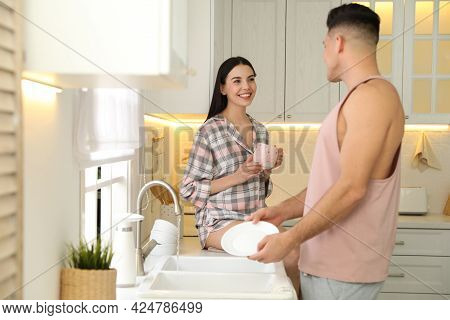 Happy Couple Wearing Pyjamas And Spending Time Together In Kitchen
