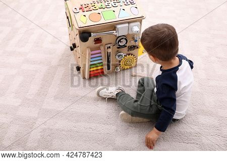 Little Boy Playing With Busy Board House On Floor Indoors
