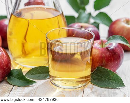 Glass of juice and carafe of fresh apple juice and organic apples on wooden table.