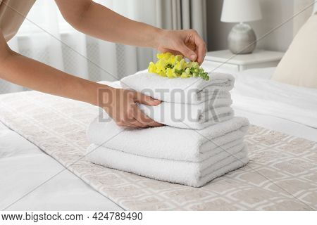 Woman Putting Flower On Fresh Towels In Room, Closeup