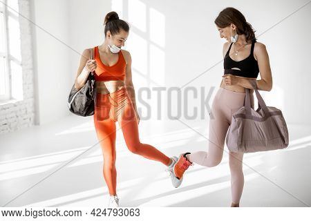 Two Sports Women In Face Masks Met In The Gym, Gathering Before The Training. New Social Rules, Wear