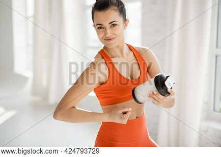 Portrait Of An Athletic Woman In Bright Sportswear With A Shaker Of Protein Drink At White Gym. The