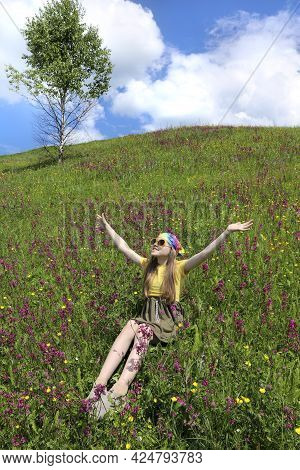 The Girl Is Enjoying Life Sitting In A Field Among Flowers With Her Arms Outstretched To The Sun.
