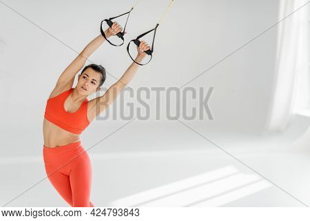 Athletic Woman Stretching With Suspension Straps, Doing Total Resistance Exercise Indoors. Image Wit