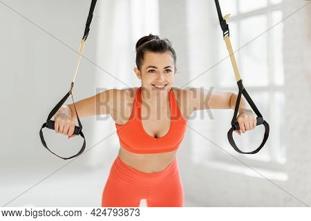 Athletic Woman Squeezing On Suspension Straps, Doing Trx Exercise At White Gym