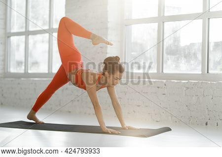 Athletic Woman In Bright Sportswear Practising Hatha Yoga, Holds Confidently A Pose On A Yoga Mat Ne
