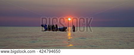 A Group Of Tourists On An Inflatable Banana At Sunset.. Inflatable Banana Shaped Boat At Sunset. Fun