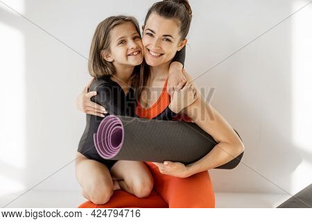 Portrait Of A Cheerful Sports Mom And Little Daughter Sitting Together With Yoga Mats During Sports