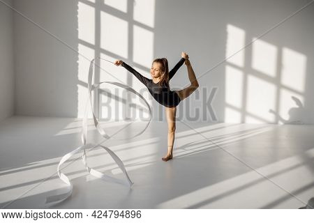 Little Girl Practising Rhythmic Gymnastics With A Gymnastic Tape At White Sunny Dance Room. Wide Vie