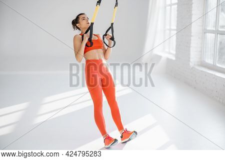 Athletic Woman In Bright Sportswear Doing Cardio Training On Suspension Straps At White Gym. Trx Tra