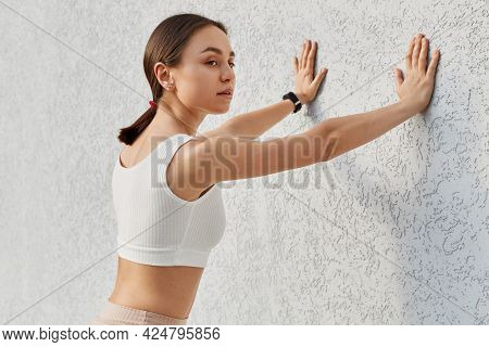 Good Looking Brunette Young Woman Wearing White Sporty Top Posing Near Gray Wall Outdoor, Touching W