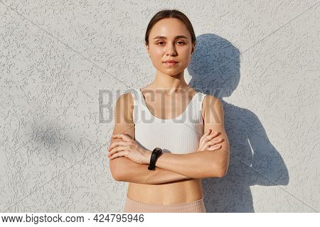 Satisfied Confident Active Healthy Dark Haired Woman In Sports White Top With Folded Arms, Looking D