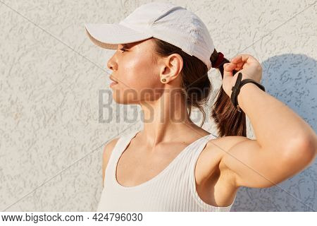 Portrait Of A Beautiful Sporty Young Adult Woman With Stylish White Top And A Visor Cap Posing Again