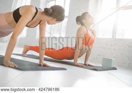 Two Athletic Women In Bright Sportswear Stretch In A Yoga Class. Trainer And Client Practicing Hatha