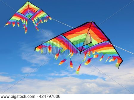 Two Large Colorful Kites Flying High In The Sky With Brightly Colored